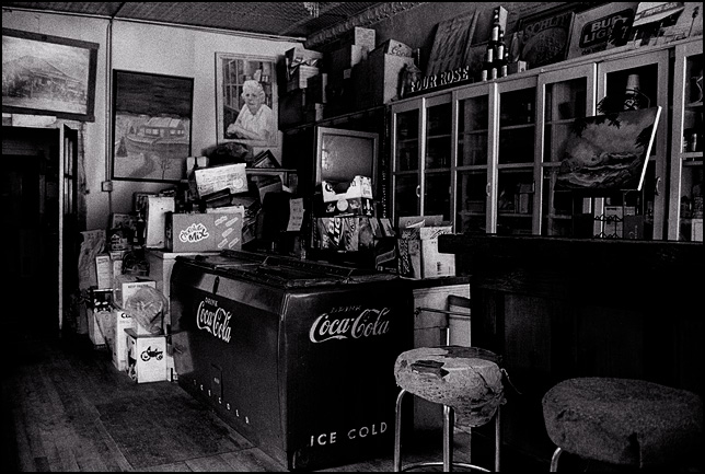 An old Coca-Cola refrigerator surrounded by piles of junk and old boxes in the back corner of Mary's Bar in Cerrillos, New Mexico.