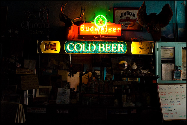 A lighted sign that says Cold Beer and a neon Budweiser sign glow in the darkness at Mary's Bar in Cerrillos New Mexico.