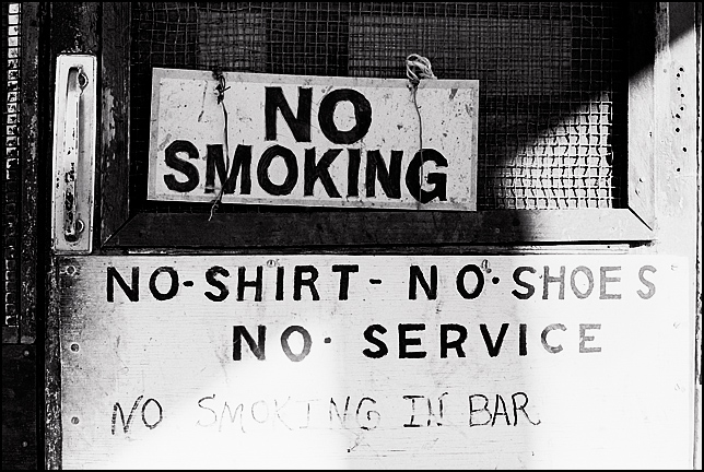 The front door of Mary's Bar in Cerrillos, New Mexico has two no smoking signs and a handpainted sign that says No Shirt, No Shoes, No Service.