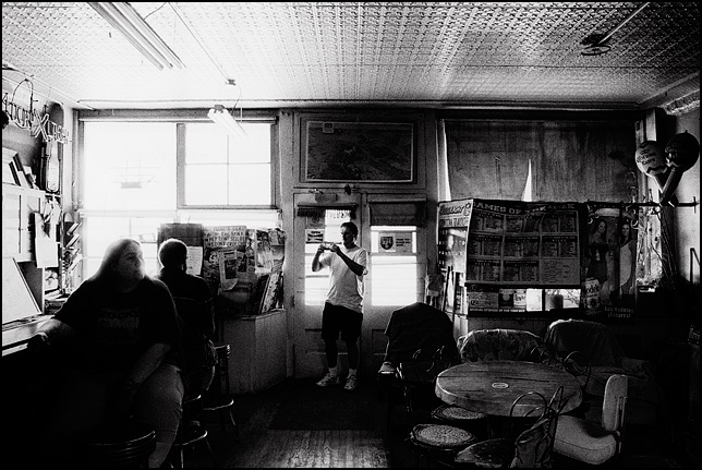 A tourist takes a photo with a digital camera inside Mary's Bar in Cerrillos, New Mexico. The old tin ceiling and old beer signs and sports posters are visible in the old saloon.