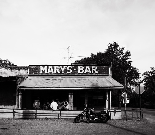 Bikers drink on the front porch at Mary's Bar in Cerrillos, New Mexico and a motorcycle is parked in front of the building. The bar is an old west structure built in 1918 and is built of adobe with a tin roof. An American flag flies from the porch and a television antenna is mounted on the roof.