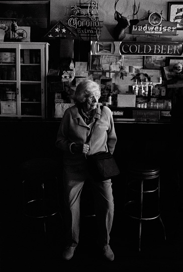 An elderly woman tourist looks uncomfortable as she leans against a bar stool at Mary's Bar in Cerrillos, New Mexico.