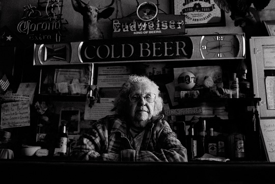 Elderly bartender Mary Mora behind the counter of Mary's Bar in Cerrillos, New Mexico. The wall behind the bar is covered in old neon beer signs from Budweiser, Jim Beam, and Corona. There are several patriotic signs and American flags and a mounted deer head and owl.