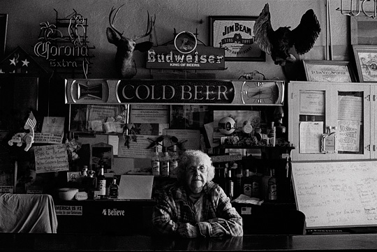 Old bartender Mary Mora behind the counter of Mary's Bar in Cerrillos, New Mexico. The wall behnd the bar is covered in old neon beer signs from Budweiser, Jim Beam, and Corona. There are several patriotic signs and American flags and a mounted deer head and owl.