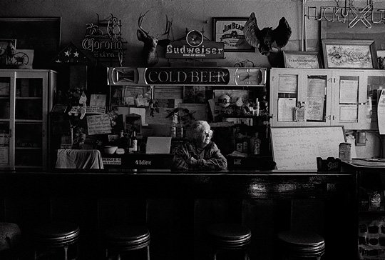 Mary Mora sits behind the counter of her bar. Old metal bar stools sit in front of the wooden bar and old cabinets hang behind it.