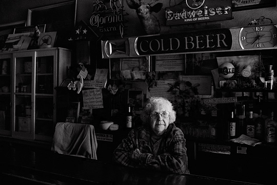 Ninety year old bartender Mary Mora behind the counter of Mary's Bar in Cerrillos, New Mexico. The wall behind the bar is covered in old neon beer signs from Budweiser and Corona. There are several patriotic signs and American flags and a mounted deer head.