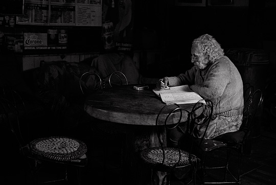 Elderly bartender Mary Mora works on a word find puzzle book late at night in her bar in Cerrillos, New Mexico.