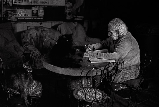 Old bartender Mary Mora sits at the table in her bar doing word find puzzles while two of her cats keep her company.