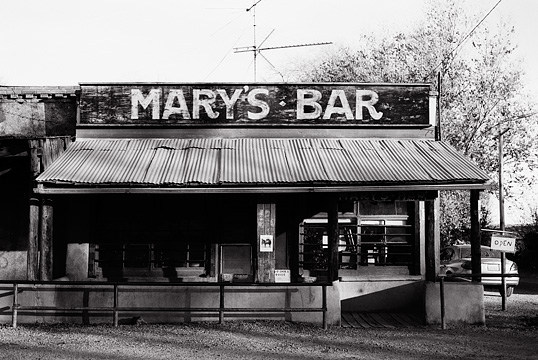 The front of Mary's bar in Cerrillos, New Mexico. The bar is an adobe building with a tin roof that looks like an old west saloon. A hitching rail stands in front of the porch.