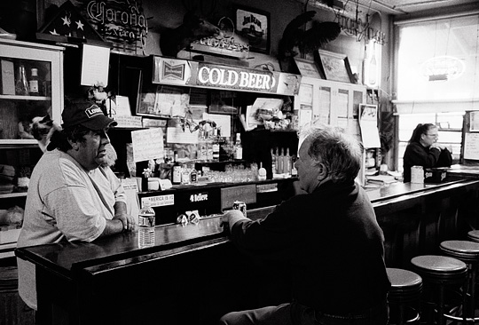 The bartender at Mary's Bar in Cerrillos, New Mexico talks to a customer while a cat sits on his shoulders.