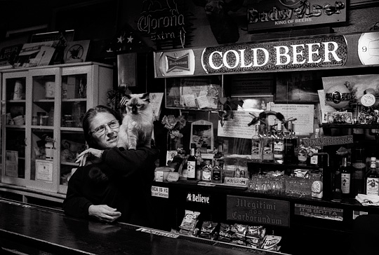 A bartender stands behind the bar with a cat on her shoulders at Mary's Bar in the small town of Cerrillos, New Mexico.