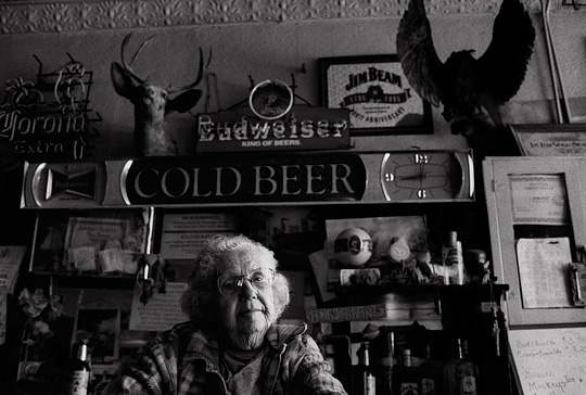Old bartender Mary Mora sits behind the counter of her small town bar in Cerrillos, New Mexico surrounded by old beer advertisements and liquor bottles. A mounted deer head and an owl hang on the wall behind the bar.