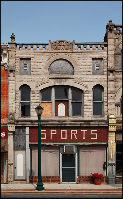 The McCrea building, a beautiful century-old commercial building with a stone facade in Wabash, Indiana. The sign above the storefront windows says SPORTS. The upper-story windows are boarded-up.