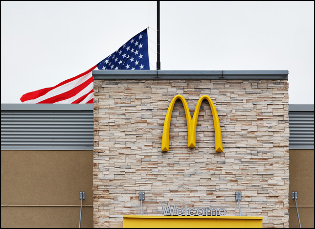 An enormous American flag behind a McDonalds restaurant.