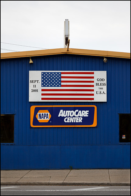 A sign that says September 11, 2001 God bless the USA above a NAPA auto repair sign at Mechanix Unlimted in Fort Wayne, Indiana.
