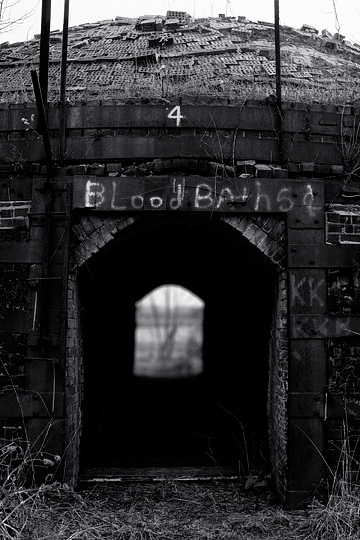 "The phrase ""Blood Baths"" has been spray painted on the metal door frame over the entrance to a beehive kiln at the abandoned brick factory in Medora, Indiana. The dome over the top of the kiln is covered in old bricks."