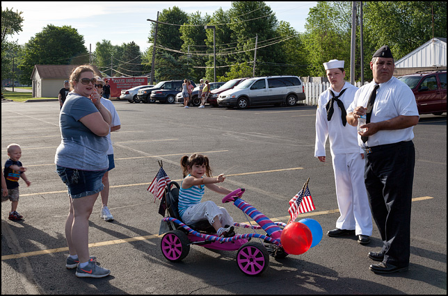 A little girl surrounded by her family rides a pedal car decorated with American flags and patriotic balloons in the staging area of the Waynedale Memorial Day Parade.