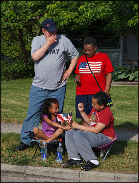 A family with two children waits for the 2016 Waynedale Memorial Day Parade to begin on Old Trail Road in the Waynedale area of Fort Wayne, Indiana. The kids are laughing and playing with the little American flags that a veterans group gave out earlier.