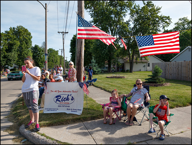 Two young children sit with their grandmother under an American flag watching the 2016 Waynedale Memorial Day Parade on Old Trail Road in the Waynedale area of Fort Wayne, Indiana. The kids and grandma are all wearing clothes with the American flag on them. A young woman standing on the edge of the road photographs the parade with her cellphone camera.