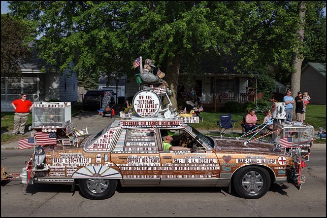 A 1978 Pontiac Bonneville art car at the 2016 Waynedale Memorial Day Parade. The car belongs to a group called Veteran For Earned Healthcare. It is covered in signs demanding better healthcare and benefits for war veterans, American flags, and motorized animals. The top of the car has a wheelchair with a life-size mannequin dressed as a soldier.