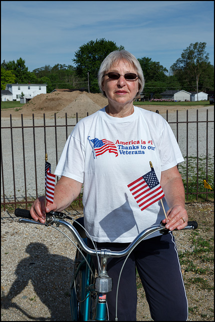 A woman on a bicycle watching the 2016 Waynedale Memorial Day Parade. She is holding American flags in both hands and is wearing a t-shirt that says, America is #1 thanks to our veterans.