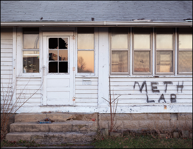 An abandoned house with graffiti painted under the window that says Meth Lab. The house is on Bluffton Road in the Waynedale area of Fort Wayne, Indiana.