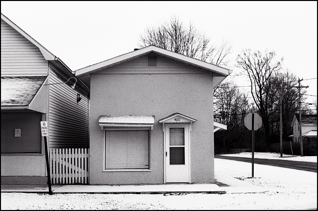 A small house or storefront on the main street of Mexico, Indiana in the winter with snow covering the sidewalks.