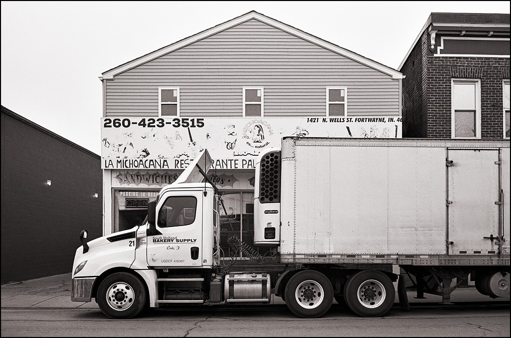 A semi truck from a restaurant supply company parked on the street in front of Paleteria La Michoacana on Wells Street in Fort Wayne, Indiana. The truck belongs to South Holland Bakery Supply.