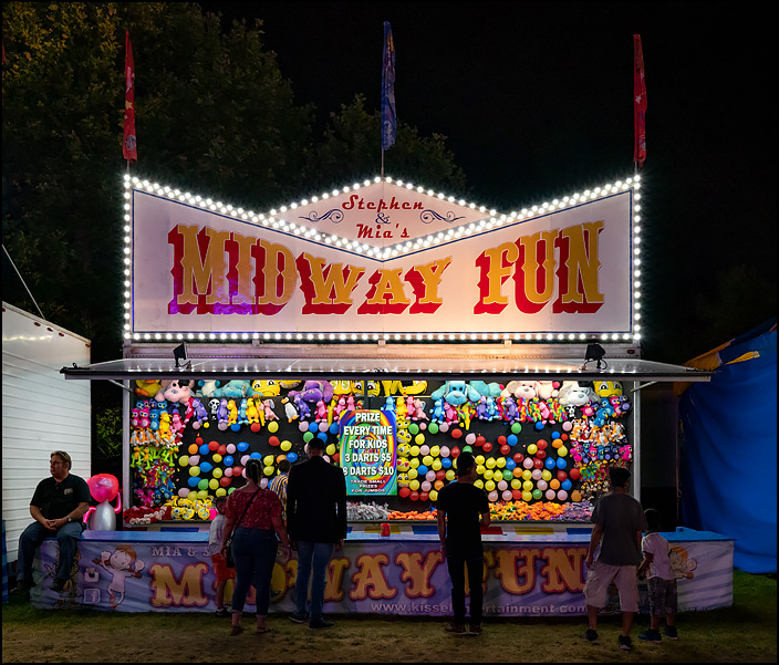 Stephen and Mias Midway Fun is a balloon dart game at the 2019 Three Rivers Festival in Fort Wayne, Indiana. Photographed at night, the colorful lights glow in the darkness.