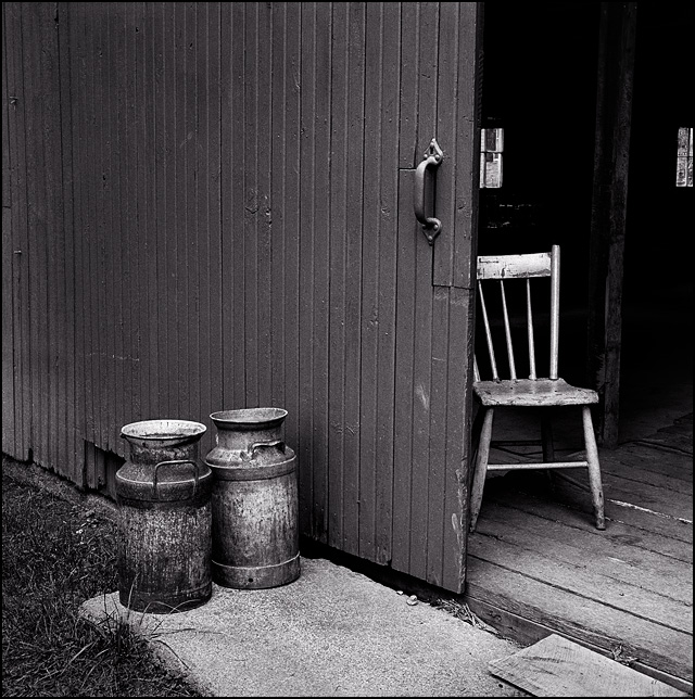 An old wooden chair sits inside a barn, and two rusty antique milk cans sit outside next to the door.