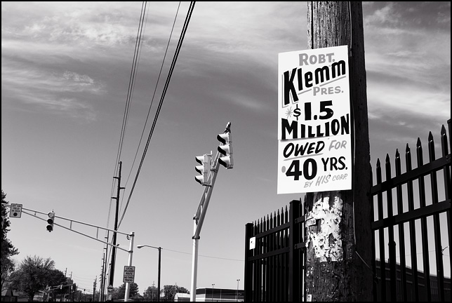 A sign posted to a utility pole at the corner of Taylor Street and Brooklyn Avenue in Fort Wayne, Indiana. The sign says Robert Klemm $1.5 Million Owed by his corporation for 40 years.