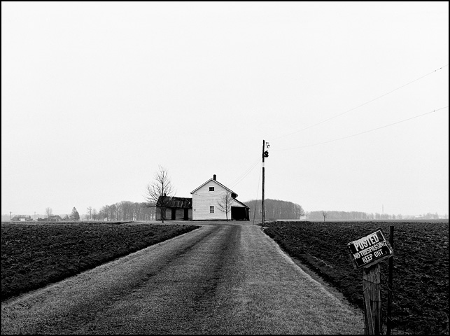 An abandoned white clapboard farmhouse in the middle of a plowed field at the end of a long driveway with a no trespassing sign at the corner of Minnich Road and Monroeville Road near Hoagland, Indiana.