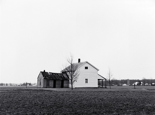 An abandoned farmhouse in the middle of a plowed field on Minnich Road in Allen County, Indiana. A well pump handle stands next to the house.