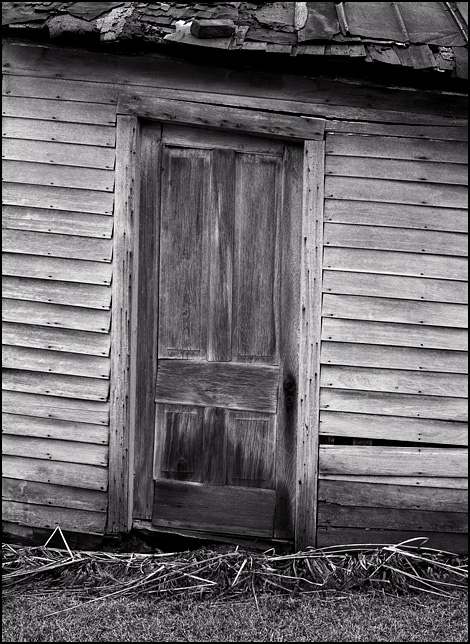The weathered wood door of an abandoned farmhouse on Minnich Road near Hoagland, Indiana. The dilapidated house looks like it is sagging and falling over.