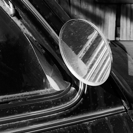 The passenger side mirror on a rusty old 1947 Chevrolet sedan.