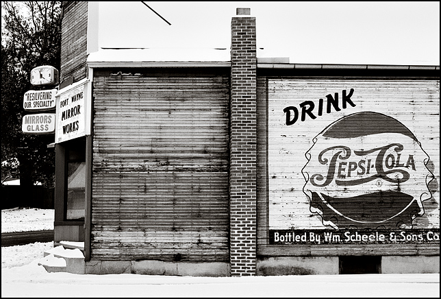 The old Fort Wayne Mirror Works building on Broadway has an old Pepsi-Cola advertisement painted across the side of the building next to the brick chimney and a clock on the front of the building. The Pepsi ad says it is bottled by William Scheele and Sons.