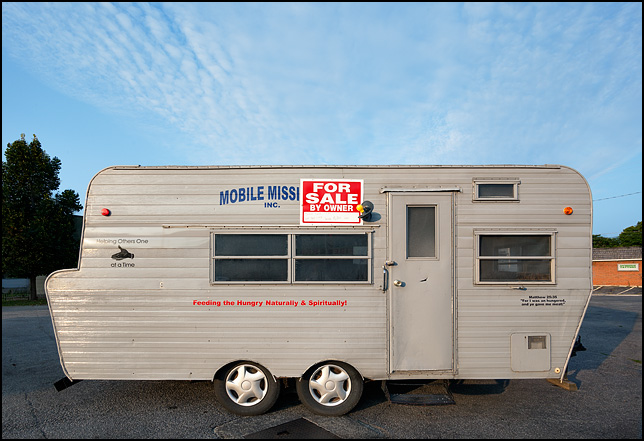 "A foodservice trailer used to feed the poor by a group called Mobile Missions sits with a for sale sign on it at the corner of Spring Street and Sherman Boulevard in Fort Wayne, Indiana. There is a Bible verse from Matthew 25 painted on it. ""For I was an hungered and ye gave me meat."""