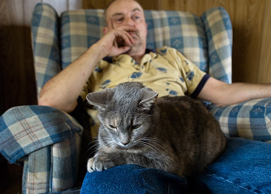 My grandfather's mean old cat sits on my uncle Danny Smith's lap at grandpa's house.
