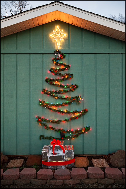 A christmas tree made of green garland and a string of colored Christmas lights hangs on the front of a house with several boxes wrapped in silver giftwrap on the ground under it.