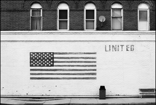 A large American flag painted on the side of an old brick building in the small town of Monroeville, Indiana. The word United is painted above a park bench next to the flag and a row of arched windows lines the top floor of the old commercial building which houses a pizza parlor. Located on Indiana State Road 101, which is Monroeville's main street. A satellite dish hangs between the windows.