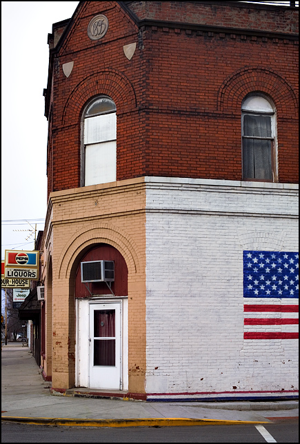 An old brick storefront building and pizzeria with an American Flag mural at the corner of South Street and Main Street in the small town of Monroeville, Indiana. The date on the medallion above the door in the corner of the building is 1898.