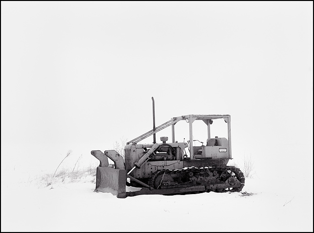 A bulldozer sits alone in a snow covered field in a heavy fog along Monroeville Road in rural southeast Allen County, Indiana.