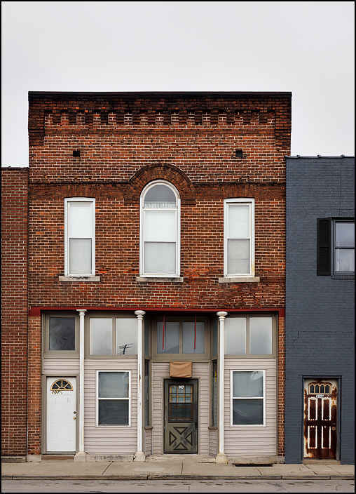 An old vacant brick storefront building on South Street in the small town of Monroeville, Indiana. The second floor has an arched window in the middle.