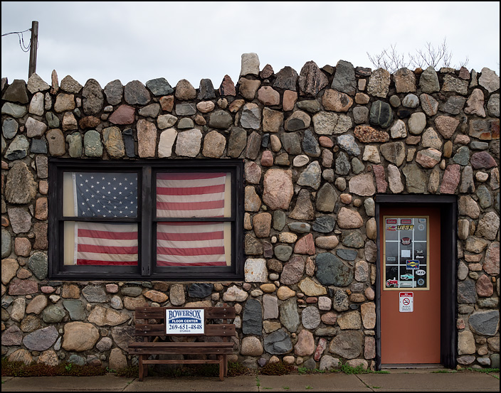 An American flag covers the front window of Jack Moore Upholstery, an automotive upholstery shop in a small fieldstone building on US-12, just east of Sturgis, Michigan.