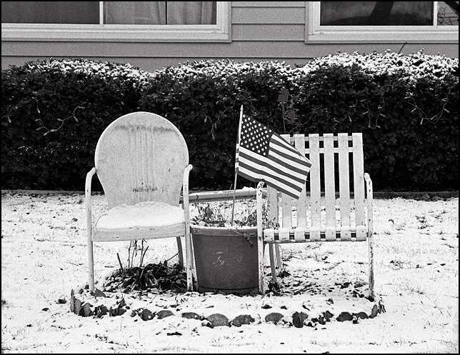 A pair of white metal patio chairs, one a motel chair, sit together in the snow-covered front yard of a house in the Belle Vista neighborhood in Fort Wayne, Indiana. An American flag is planted in a large flowerpot between the chairs.