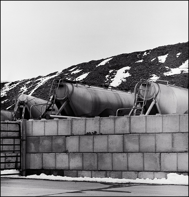Several bulk goods trailers sit behind a concrete wall in front of of a snow covered mountain of overburden from a limestone quarry.