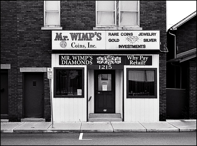 The former Mister Wimp's Coin and Jewelry store in an old brick storefront on Wells Street in Fort Wayne, Indiana. The signs on the building advertise jewelry, gold, rare coins, and investments.