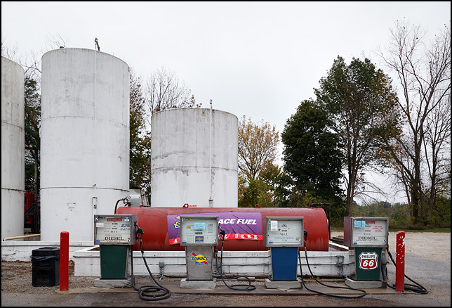 Four old gas pumps in front of several large fuel tanks at a gas station on State Road 14 in South Whitley, Indiana.