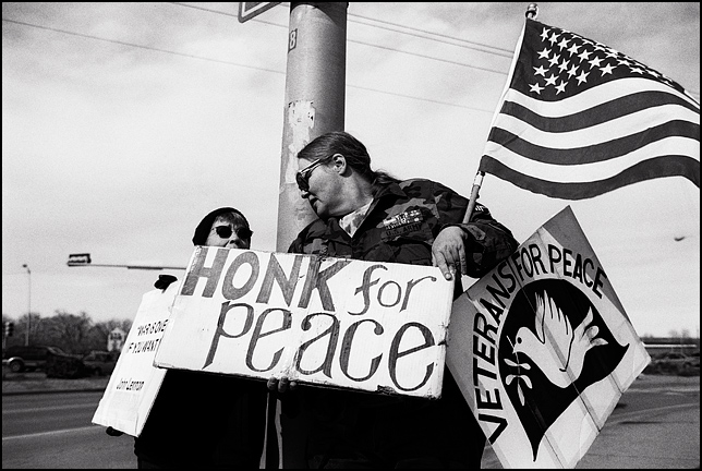 A female army veteran and a member of Veterans for Peace holds a large American flag and a sign that says Honk For Peace. She is talking to an older woman who is also protesting the war in Iraq.