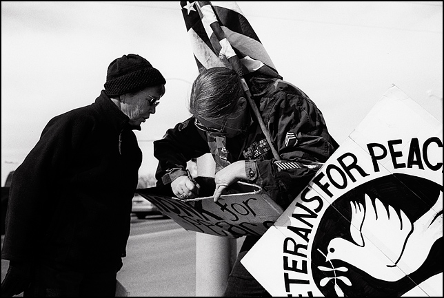 Two peace activists exchange names and phone numbers during the weekly antiwar protest in Santa Fe. One is a veteran in her Army uniform holding a large American flag and a Veterans For Peace sign.